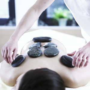 Hot stones being placed at pressure points on a person's back