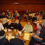 Quiz participants sitting at their team tables, some tucking into their fish and chips, others filling in the Marathon Round answer sheet
