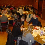 Quiz participants sitting at their team tables, tucking into their supper