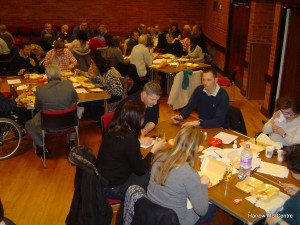 Quiz participants sitting at their team tables, tucking into their fish and chips