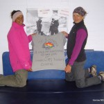 Jo and Apeksha pose in front of the photo of them at Base Camp, proudly displaying the t-shirt