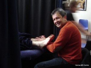 A reflexologist gives treatment to a client.