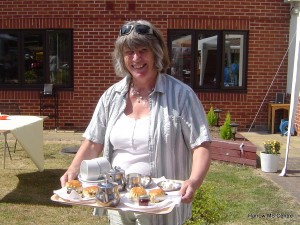 Linda Hunt, Head of Physiotherapy Services, holding a plate of scones and tea.