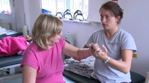 A physio helps a Harrow MS Therapy Centre patient improve her upper-limb function