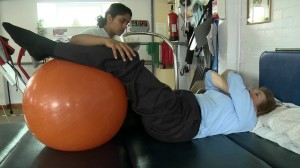 A physio helps a Harrow MS Therapy Centre patient to improve her core stability