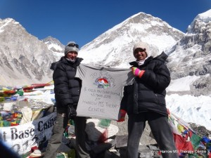 Jo and Apeksha proudly holding a t-shirt proclaiming they have reached Everest Base Camp and Kala Patthar, with the Himalayas in the background