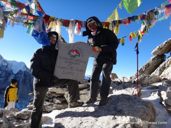 Jo and Apeksha proudly holding a t-shirt proclaiming they have reached Everest Base Camp and Kala Patthar, surrounded by traditional prayer flags