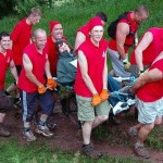 An MS Challenge team wearing matching red shirts carrying their MS passenger in her wheelchair along a muddy path