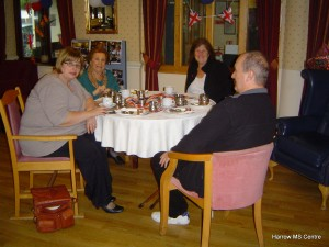 Friends having tea and coffee around a table