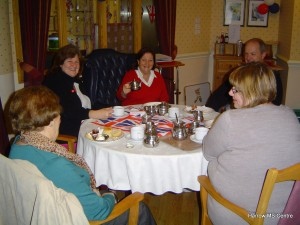 People enjoying a cream tea around the table