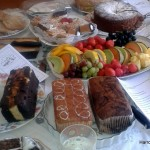 Homemade cakes and fruit platters, interspersed with flyers about Harrow MS Therapy Centre