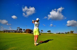 A woman driving a golf ball across a vibrant green course, against a blue sky
