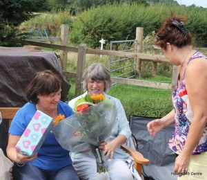 Lynn is presented with a gift of wine glasses and flowers from trustees, watched by Linda.