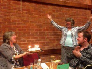 Linda is surprised by a birthday cake with candles blazing