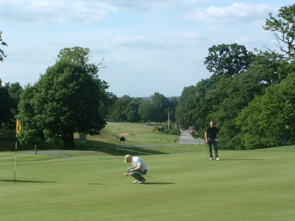 View across the fairway at Moor Park Golf Club: smooth putting green and cloudy but blue sky