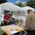 A customer examines goods on sale at our stall at the Eastcote Garden Picnic